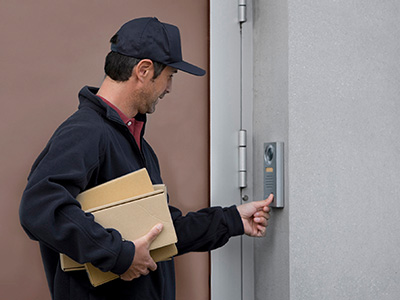A delivery person with packages under one arm, hoping to gain access to a building is using his thumb to press the call button of a wall mounted, vandal resistant video entry intercom station.