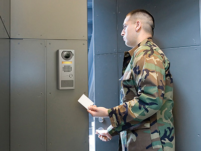 A latino soldier in camouflage is opening an access controlled, secured door after swiping his credentials in front of the card reader mounted inside an exchange-based video intercom door station. Had his credentials failed the soldier would have used the call button on the exchange-based video intercom door station to request entry.