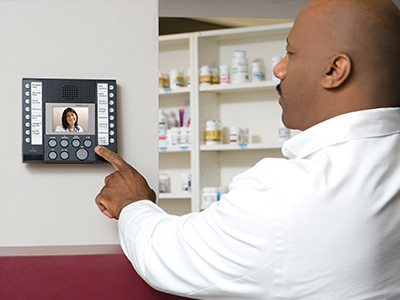 From the secured side of a pharmacy door, a pharmacist is using an exchange-based video intercom master mounted to a wall to clearly see and speak with a nurse or doctor requesting entry