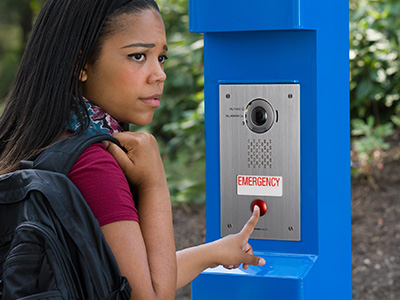 Darker skinned woman with black hair, obviously a student on a campus, holding a backpack, looking apprehensively to her right as she calls for assistance using an Aiphone IX Series 2 emergency solution video intercom mounted in an Aiphone blue modular tower.