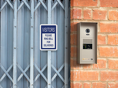 A hooded, weather resistant multi-tenant video entry station made from zinc die cast is mounted to the surface of a brick wall next to an accordion security gate to allow legitimate visitors a method to request entry into the building.