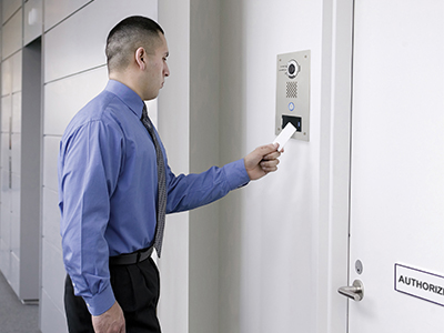 Business person presenting a key card to an IX-DVF-P to gain access to a locked door. Should the key fail the video intercom can be used to request entry.