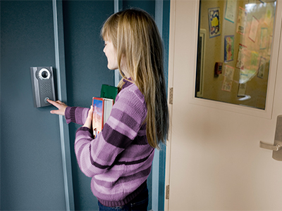 School aged child using an IX Series 2 IP video intercom unit to request entry into a secured school building