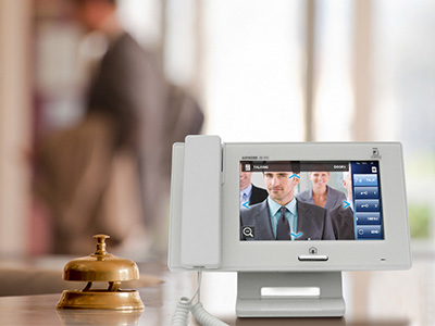 A touchscreen master mounted on a desk in a retail or hotel environment. A brass call bell sits to its left and the seven inch screen is showing a group of people awaiting entry.