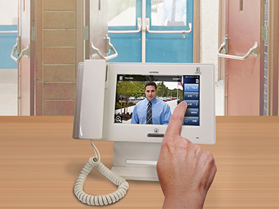A touchscreen intercom with a seven inch display sits on a wooden receptionist desk in a school and displays a young dark haired man in a blue collared shirt and tie outside the school waiting to be granted access