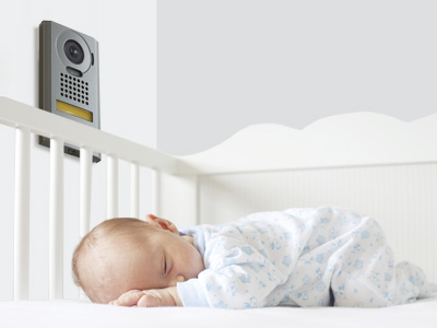 an infant in a white onesie with blue flowers sleeps soundly in it's crib, a video door station mounted to a wall allowing parents to clearly see and listen in to their child, ensuring its safety